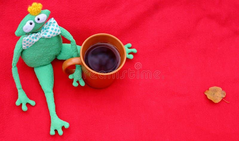 Śmieszna miękkiej części zabawki książe żaba z filiżanką herbata czeka na czerwonym chodniku, spadać liściach i obrazy royalty free