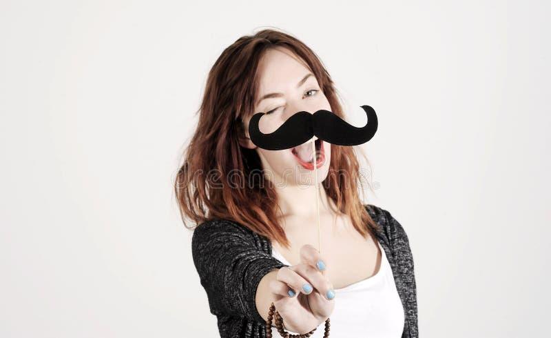 Śmieszna modna mody dziewczyna z papierowym wąsy bawić się z emocją obraz stock