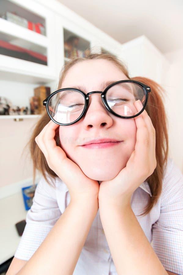 Śmieszna nerdy dziewczyna marzy o hol z ponytails w eyeglasses zdjęcia stock