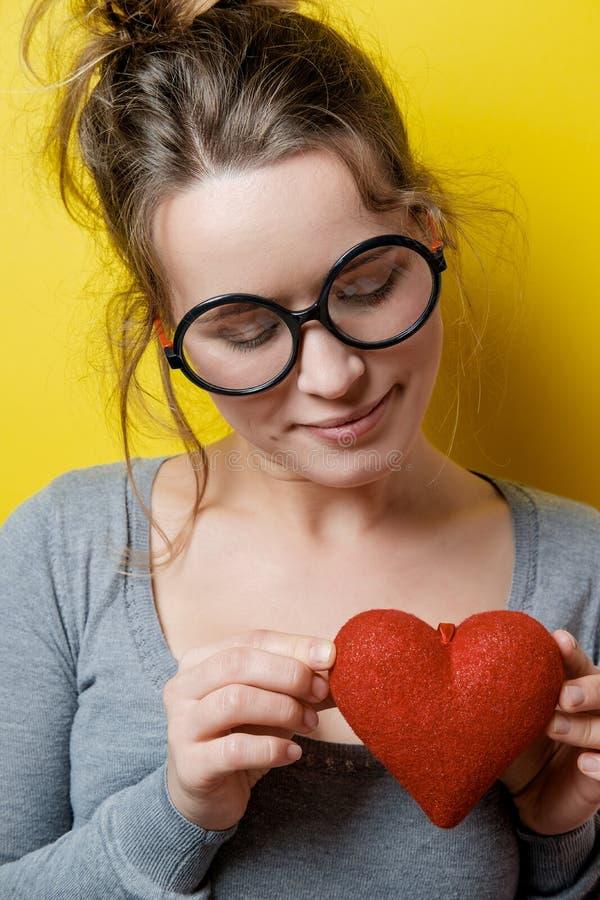Śmieszna nerdy kobieta z czerwonym sercem na żółtym tle Valen zdjęcie royalty free