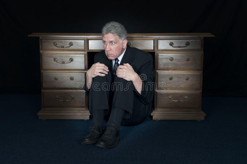 Śmieszna Okaleczająca strachu biznesmena kryjówka Pod Biurowym biurkiem zdjęcia royalty free