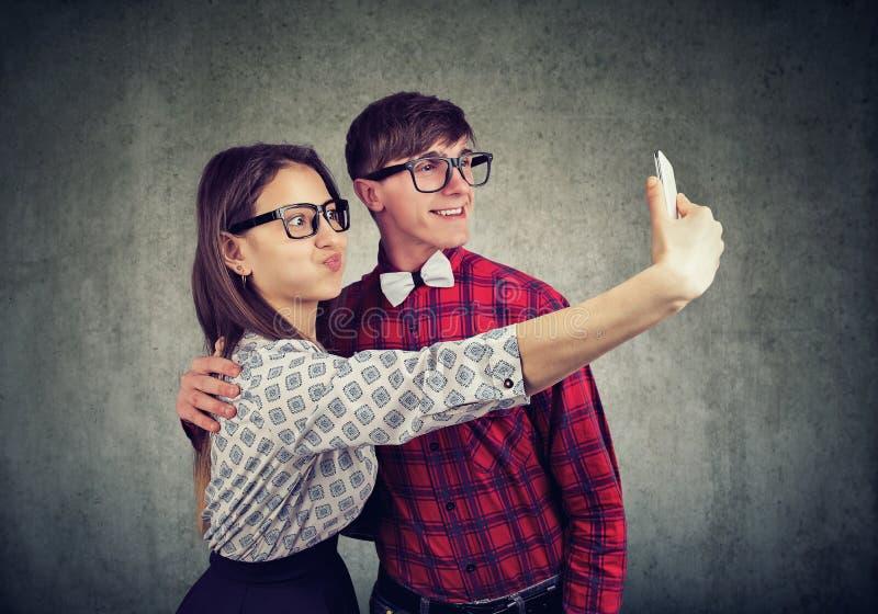 Śmieszna para robi twarzom bierze selfie na telefonie komórkowym obraz stock