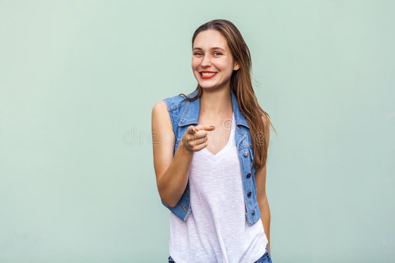 Śmieszna piegowata dziewczyna w przypadkowej bielu t koszula i cajgu jecket, wskazujący palec przy kamerą i toothy uśmiechem obraz royalty free
