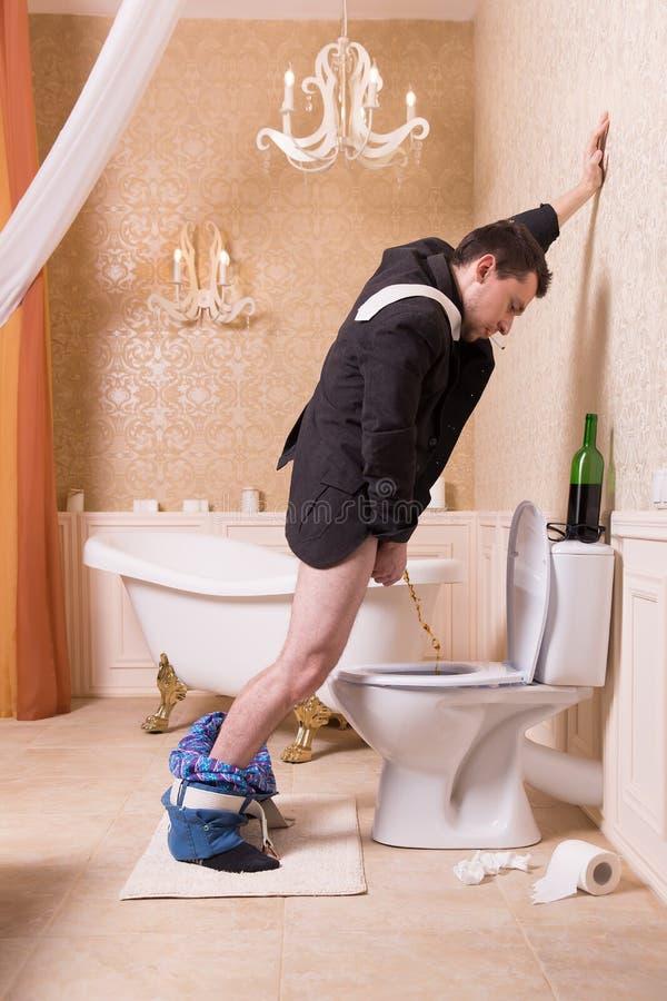 Śmieszna pijąca mężczyzna uryna w toaletowym pucharze fotografia stock