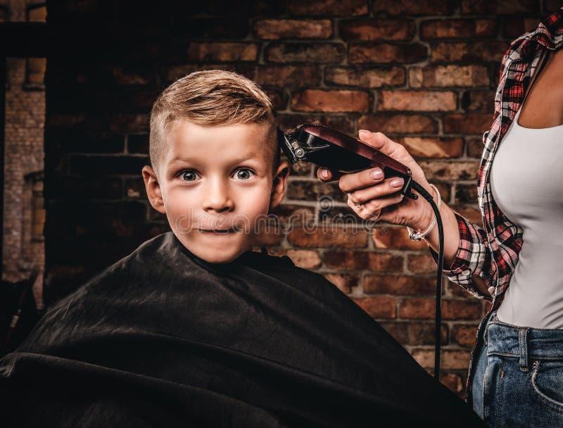Śmieszna preschooler chłopiec dostaje ostrzyżenie Dziecko fryzjer z drobiażdżarką jest tnącym chłopiec w pokoju z loft obraz stock