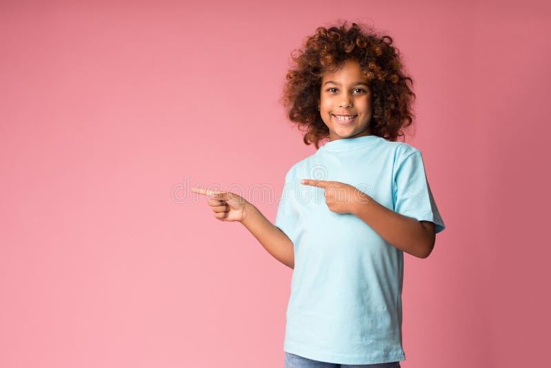 Śmieszna preteen dziewczyna wskazuje palce daleko od na bezpłatnej przestrzeni zdjęcia stock