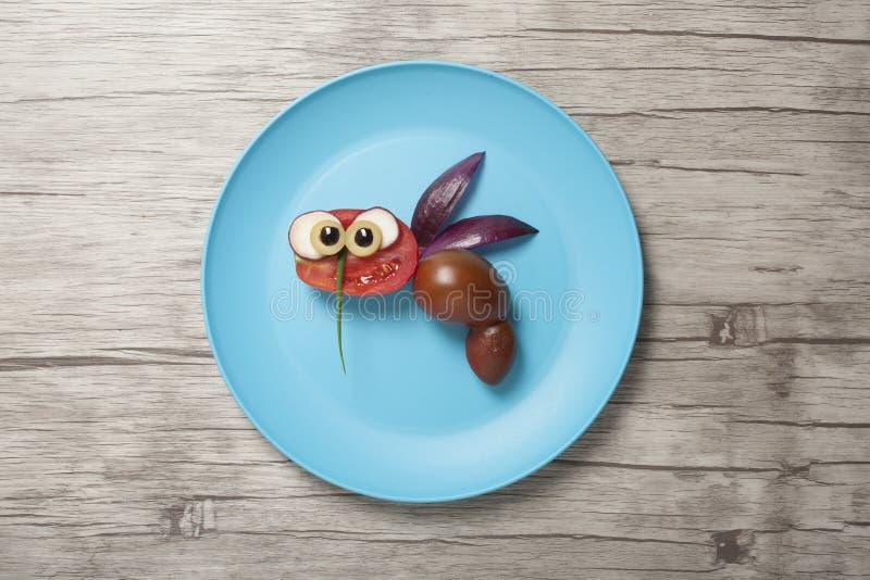 Śmieszna pszczoła robić z warzywami na talerzu i biurku fotografia stock