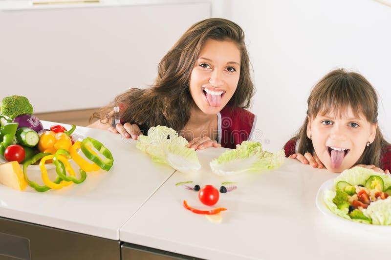 Śmieszna rodzinna robi smiley twarz z sałatką obraz royalty free