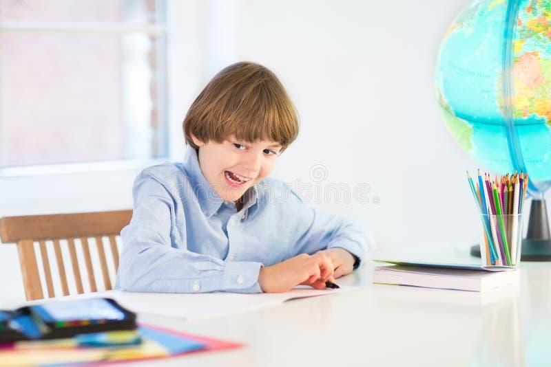 Śmieszna roześmiana chłopiec robi jego pracie domowej zdjęcia royalty free