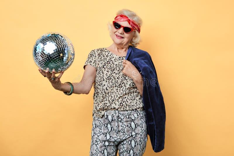 Śmieszna stara kobieta trzyma piłkę w okularach przeciwsłonecznych obrazy royalty free