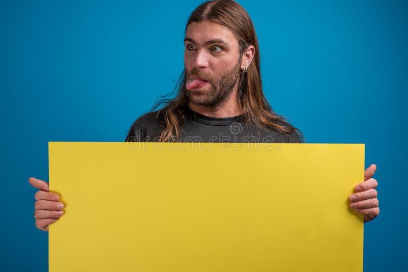 Śmieszna szalona adul samiec trzyma żółtego karton kamera z przebijaniem w jęzorze fotografia royalty free