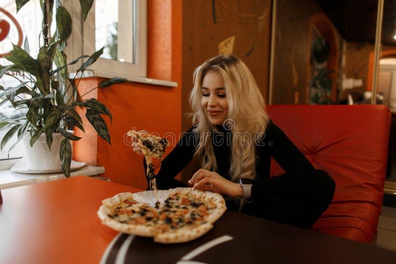 Śmieszna szczęśliwa kobieta z pizzą siedzi przy stołem w kawiarni zdjęcie royalty free