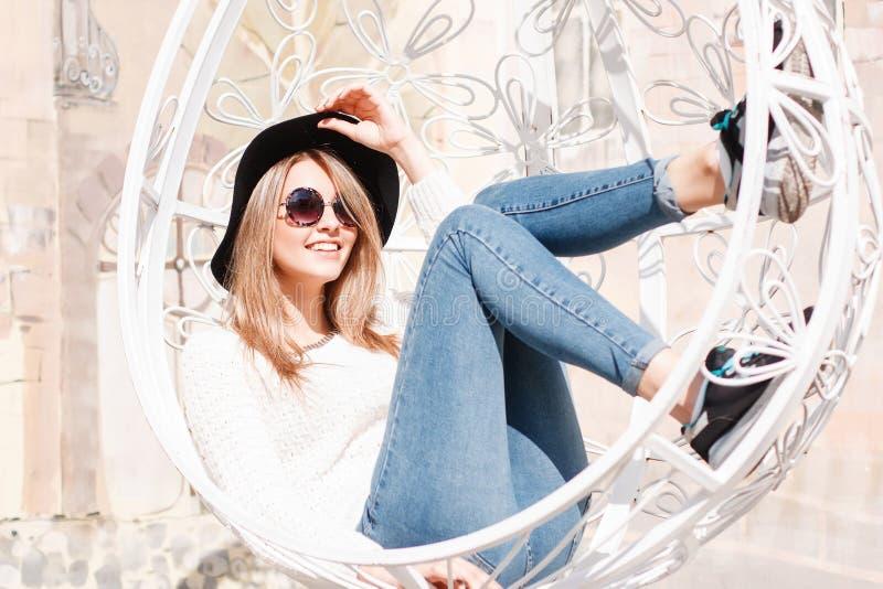 Śmieszna szczęśliwa młoda modniś kobieta w niebieskich dżinsach w trykotowym pulowerze w modnym kapeluszu w round okularach przec obrazy stock