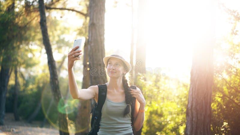 Śmieszna turystyczna dziewczyna w kapeluszu bierze selfie fotografie z smartphone kamerą podczas podróżowania i hitchhiking zdjęcie stock