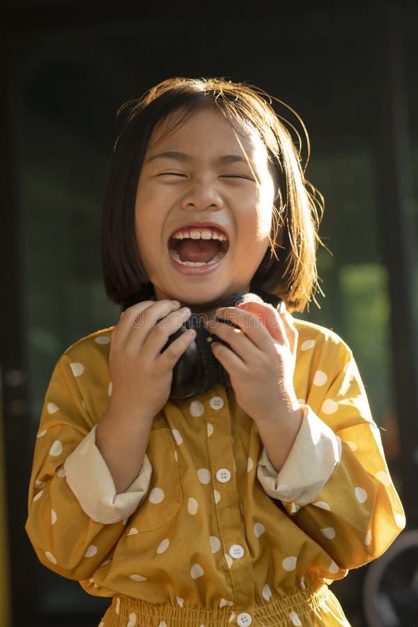 Śmieszna twarz azjatykci dzieci trzyma hełmofon w ręce fotografia royalty free