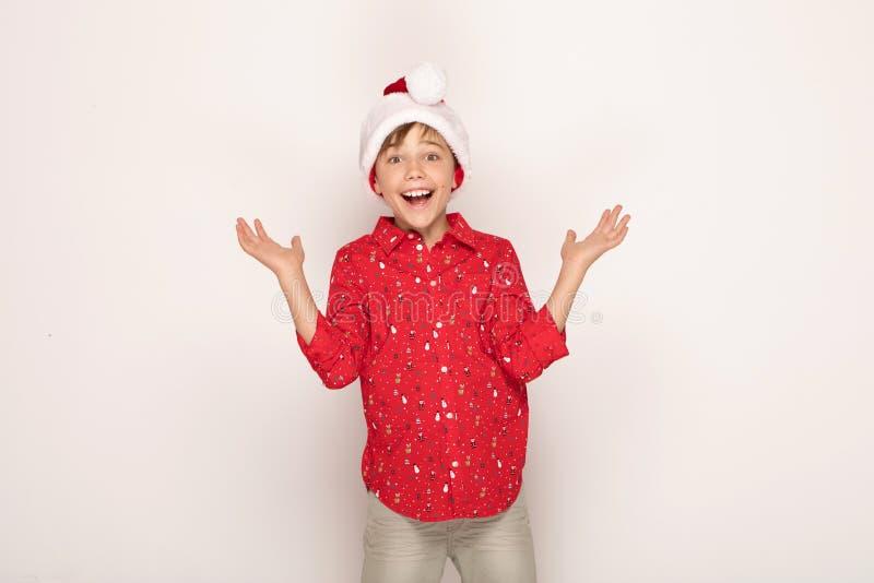 Śmieszna uśmiechnięta dziecko chłopiec w Santa czerwieni kapeluszu zdjęcie royalty free