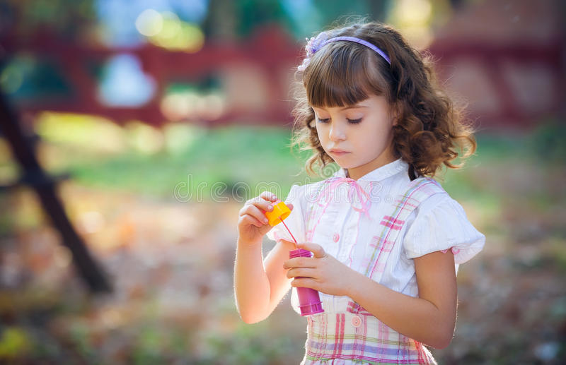Śmieszna urocza mała dziewczynka dmucha mydlanego bąbel obraz stock