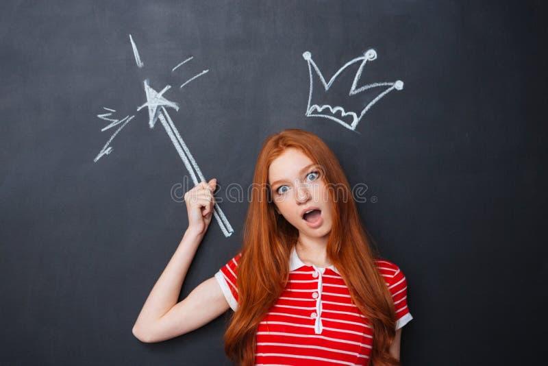 Śmieszna zadziwiająca kobieta stoi nad blackboard tłem z patroszoną koroną zdjęcia royalty free