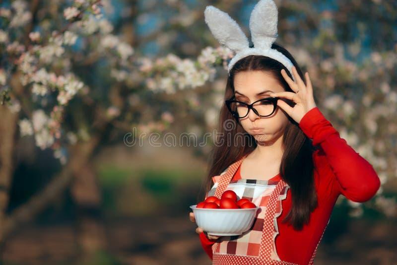 Śmieszna Zmęczona gospodyni domowa z królików ucho, fartuchem i Wielkanocnymi jajkami, fotografia stock