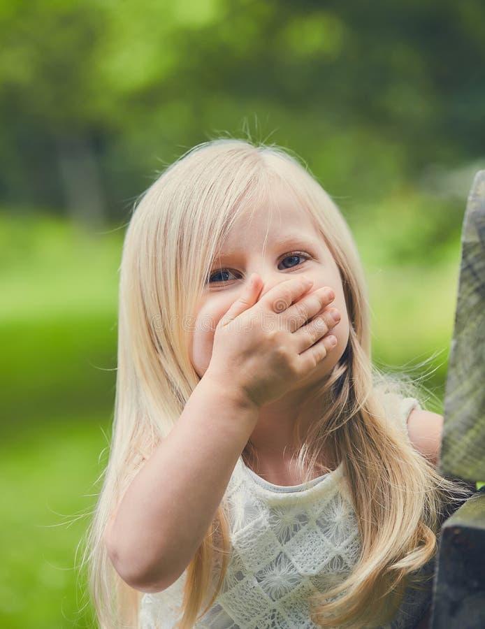 Śmiesznej małej dziewczynki roześmiany nakrywkowy usta obraz royalty free