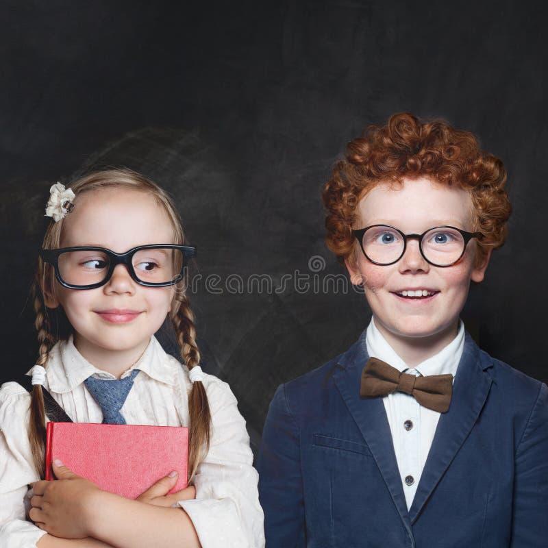 Śmieszni dzieci chłopiec i dziewczyna na blackboard tle zdjęcia stock