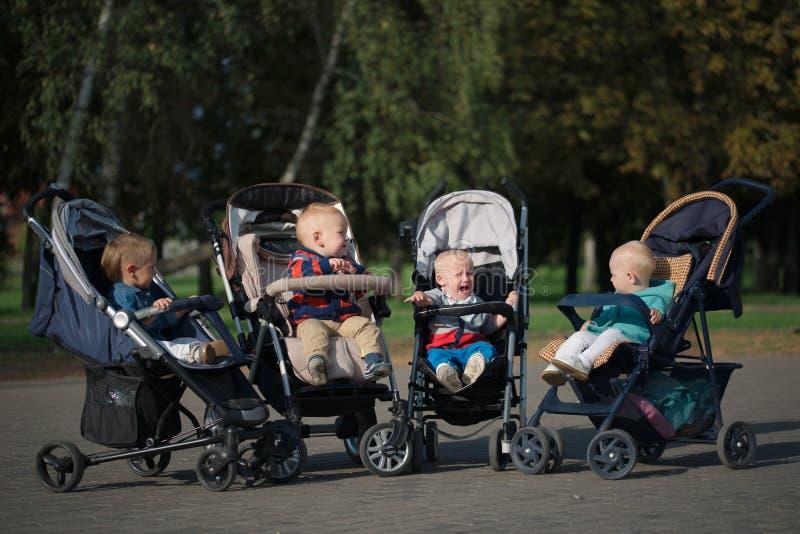 Śmieszni dzieci siedzi w spacerowiczach w parku zdjęcia royalty free