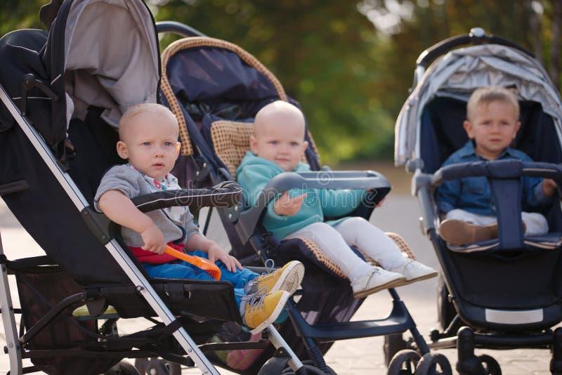 Śmieszni dzieci siedzi w spacerowiczach w parku zdjęcia stock