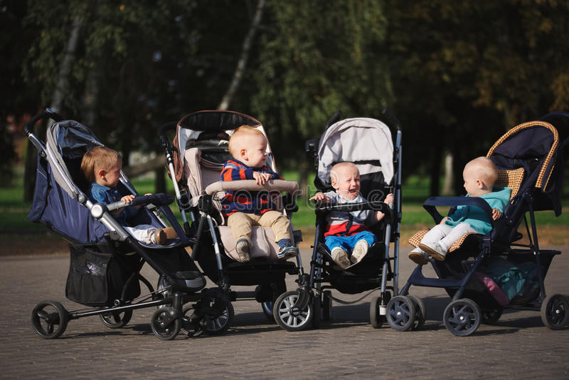 Śmieszni dzieci siedzi w spacerowiczach w parku zdjęcie stock