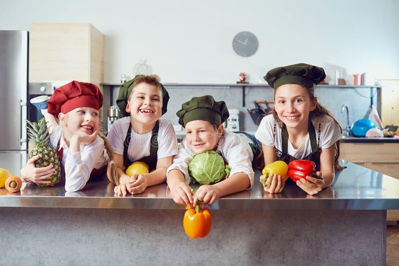 Śmieszni dzieci w mundurze kucharzi na stole w warzywie fotografia royalty free