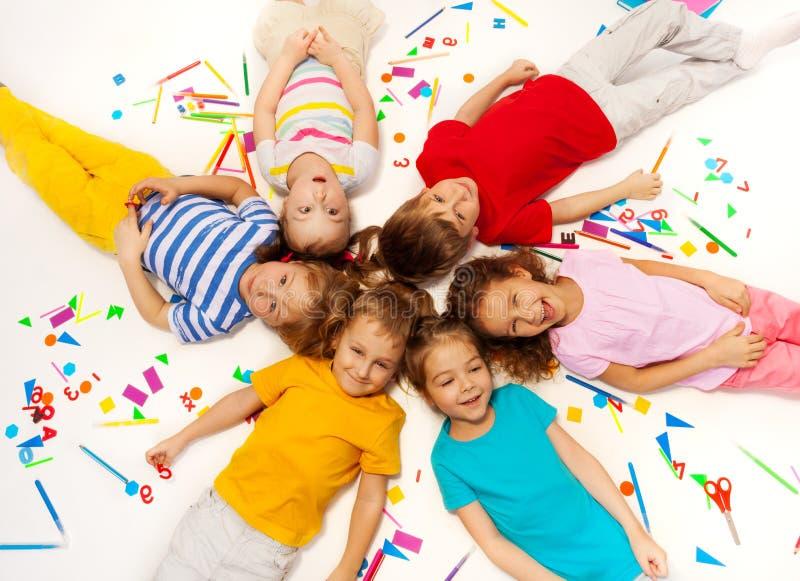 Śmieszni dzieciaki kłaść wśród szkolnych biurowych dostaw obrazy stock