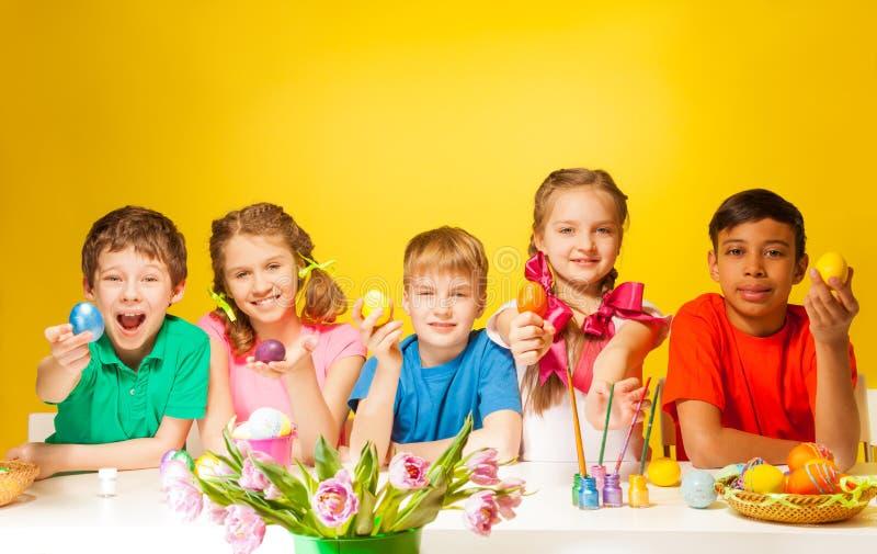 Śmieszni dzieciaki trzyma coloured Wielkanocnych jajka przy stołem zdjęcia royalty free