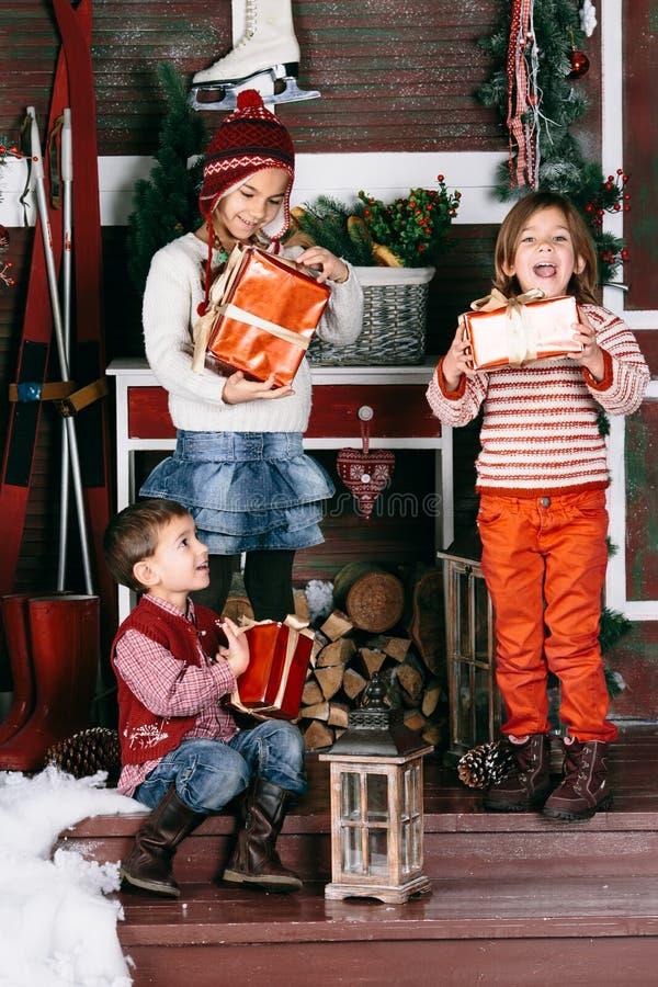 Śmieszni dzieciaki trzymają Bożenarodzeniowe teraźniejszość Pojęcie obraz royalty free