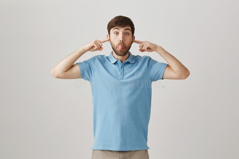 Śmieszni męscy nakrywkowi ucho z palcami wskazującymi podczas gdy robić twarzy i wtykający out jęzor, być w figlarnie nastroju, s zdjęcie stock