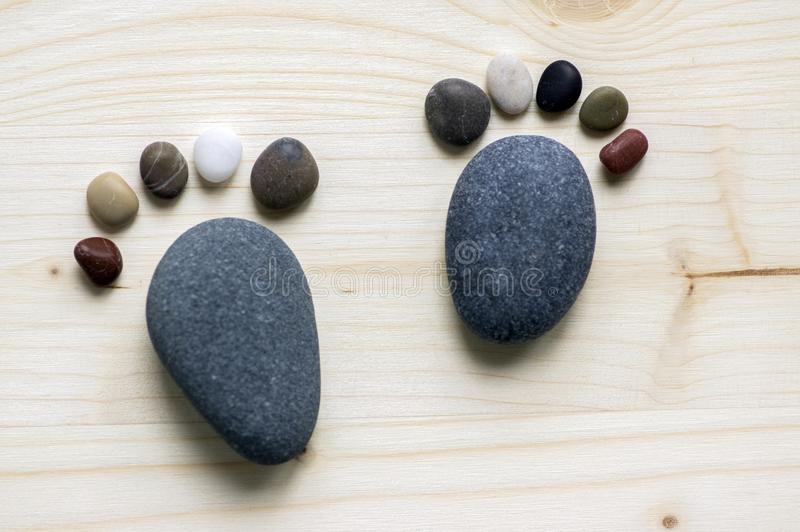 Śmieszni malutcy kamienni cieki i dziesięć palec u nogi na drewnianym tle, kamień w formie ludzkich cieków obrazy stock