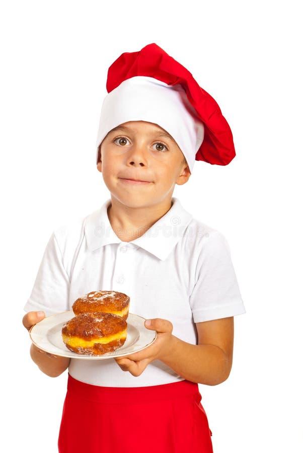 Śmieszni szef kuchni chłopiec mienia donuts fotografia stock