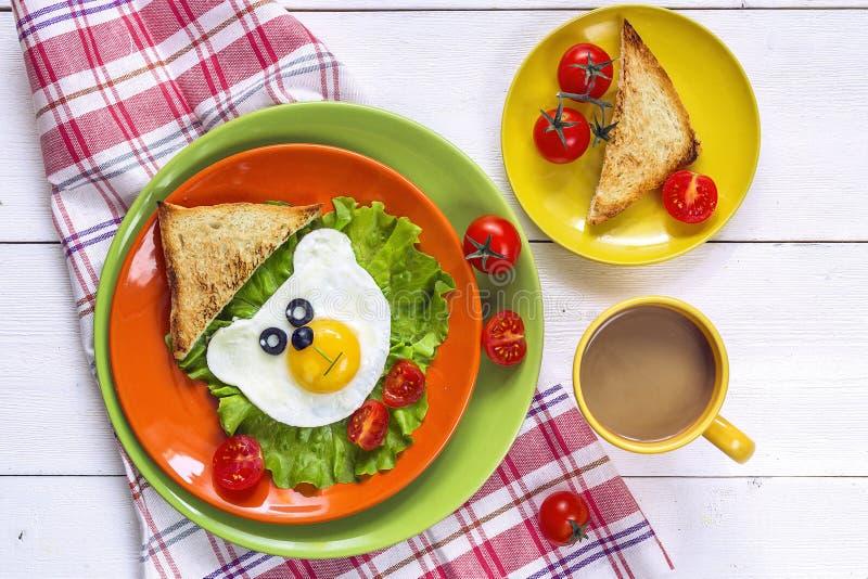 Śmieszny śniadanie z kształtującym smażącym jajkiem, grzanka, czereśniowy pomidor zdjęcie stock