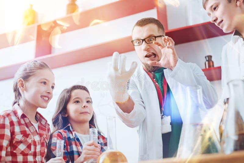 Śmieszny adiunkt robi niemądrym twarzom podczas naukowego eksperymentu z dzieciakami obraz royalty free