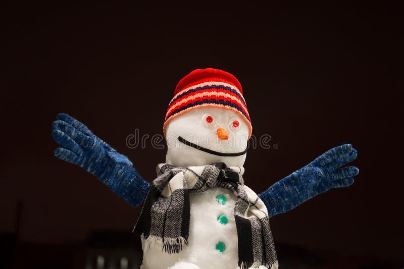 Śmieszny bałwan Piękny bałwan w czerwonej nakrętce ono uśmiecha się i ręki w górę zdjęcia stock