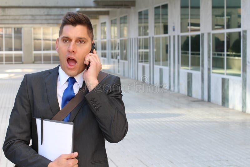Śmieszny biznesmen dostaje szokującą wiadomość na telefonie obraz stock