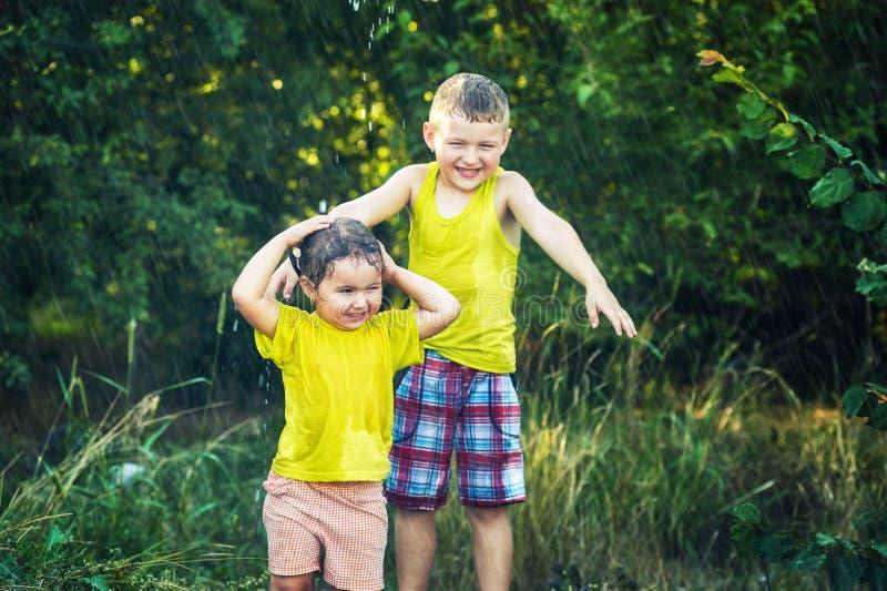 Śmieszny brat i siostra bawić się w lecie padamy fotografia stock