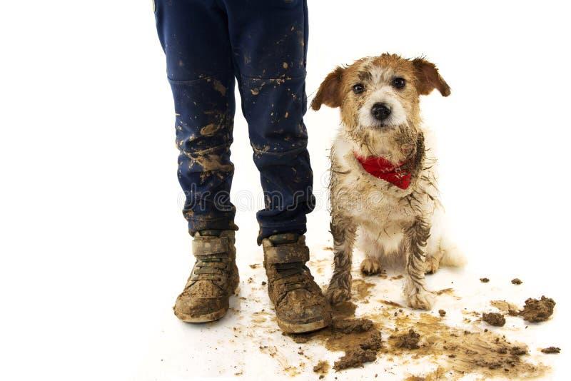 ŚMIESZNY BRUDNY pies I dziecko JACK RUSSELL pies I chłopiec JEST UBRANYM buty PO sztuki W BOROWINOWEJ kałuży Z ZAWSTYDZONYM wyraż obraz stock
