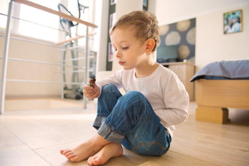 Śmieszny chłopiec obsiadanie na podłoga zdjęcie stock