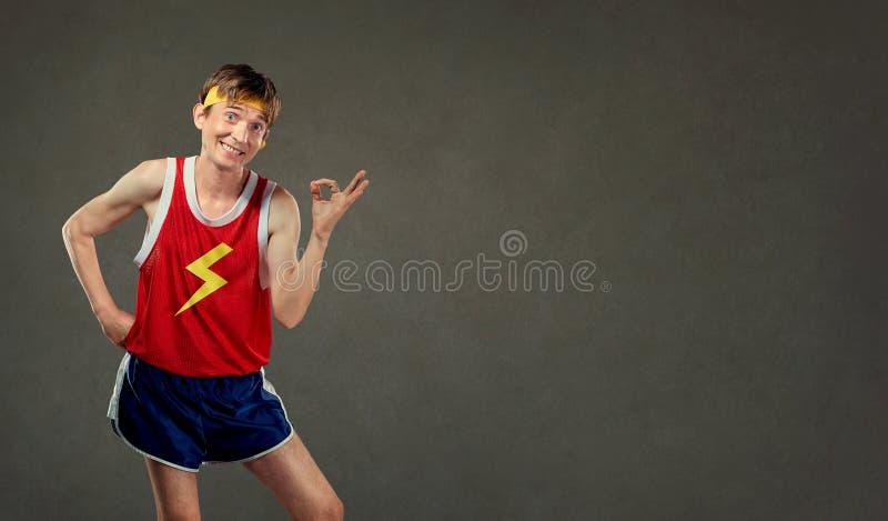 Śmieszny cienki mężczyzna w sportach odziewa przedstawienia jego ręki ok obrazy stock