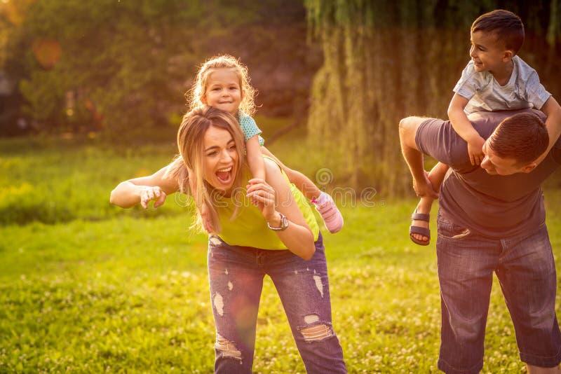 Śmieszny czas - rodzice daje piggyback przejażdżce dzieci obrazy royalty free