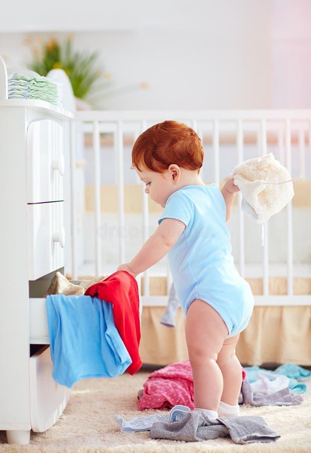Śmieszny dziecięcy dziecko rzuca out odziewa od dresser w domu obraz stock