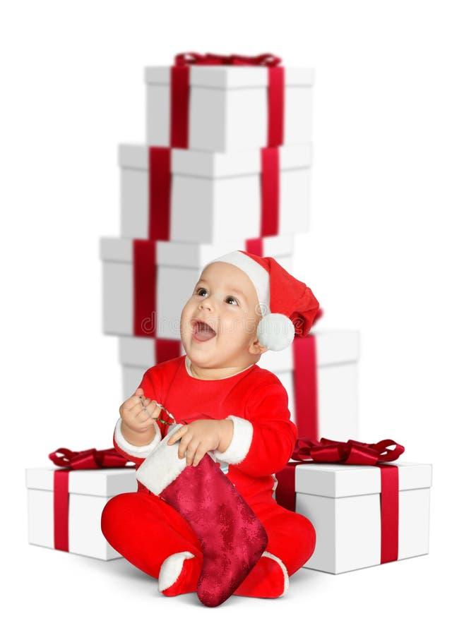 Śmieszny dziecko Święty Mikołaj z Bożenarodzeniowymi prezentami na bielu zdjęcia royalty free