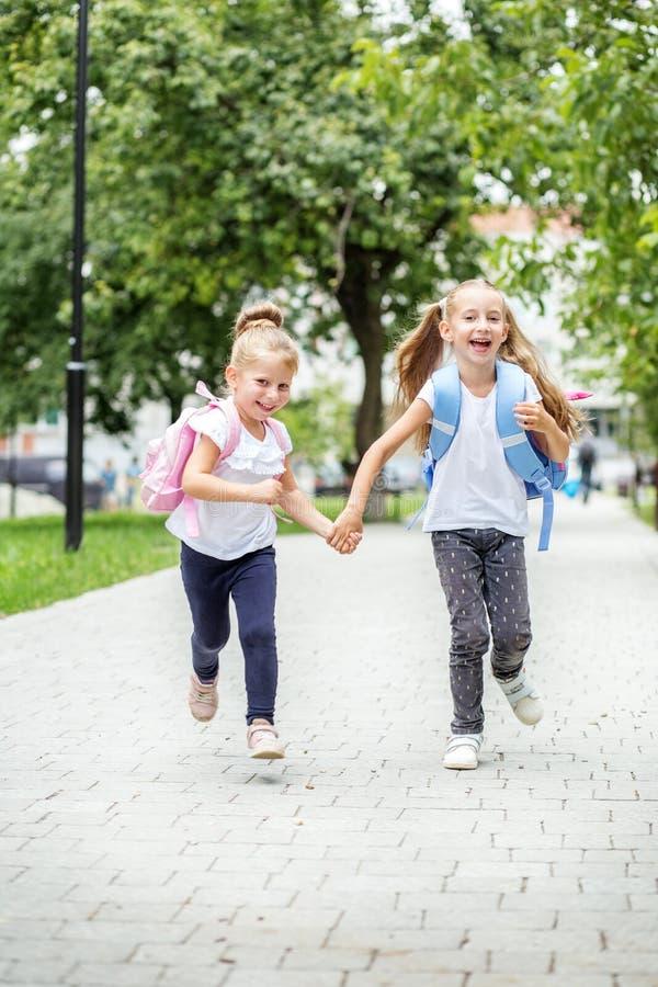 Śmieszny dziecko bieg od szkoły z plecakami Pojęcie szkoła, nauka, edukacja, przyjaźń, dzieciństwo fotografia royalty free