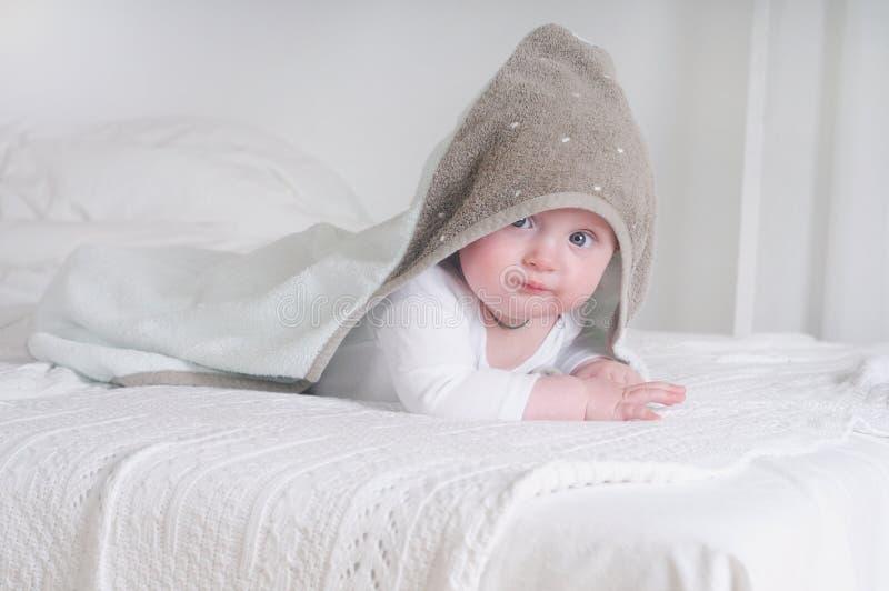 Śmieszny dziecko dzieciak pod kapturzastym ręcznikiem fotografia royalty free