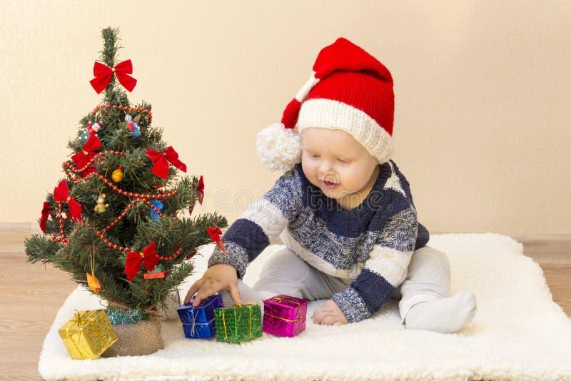 Śmieszny dziecko w Święty Mikołaj kapeluszowym obsiadaniu blisko choinki z prezentami obrazy stock