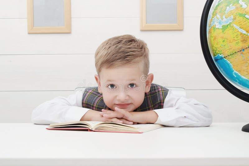 Śmieszny dziecko w szkole chłopiec z książką, dziecko edukacja obrazy stock